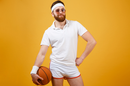 Sportsman in sunglasses which holding basketball while holding arm at hip and looking at camera. Isolated orange background Stock Photo