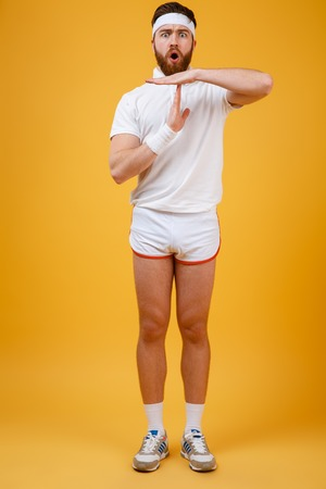 Vertical image of displeased sportsman which showing time-out sign while looking at camera. Full length portrait over orange background