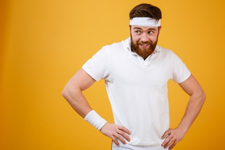 Funny bearded sportsman which holding arms at hip and looking away. Isolated orange background