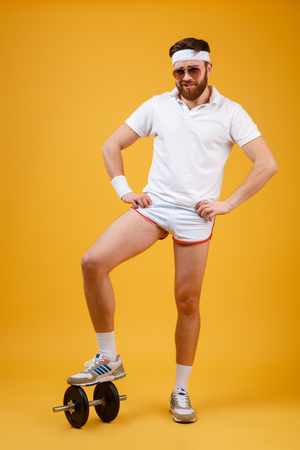 Vertical image of Funny sportsman which standing on dumbbell and holding arms at hip. FFull length portrait over orange background