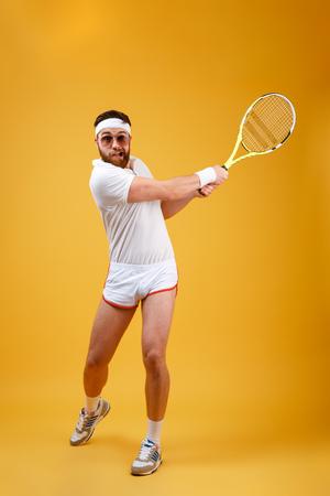 Verticaal beeld van sportman in zonnebril die in tennis spelen. Volledig lengteportret over oranje achtergrond Stockfoto