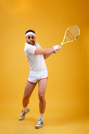 Vertical image of sportsman in sunglasses which playing in tennis. Full length portrait over orange background