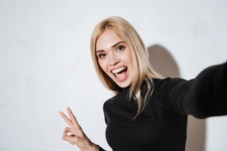Smiling excited woman making selfie and showing peace gesture in studio isolated on the white background