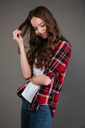 Cute shy young woman in plaid shirt and jeans standing and tounching her curly hair over grey background