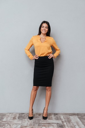 executive assistants: Portrait of successful young business woman standing with her hands in hips against gray background