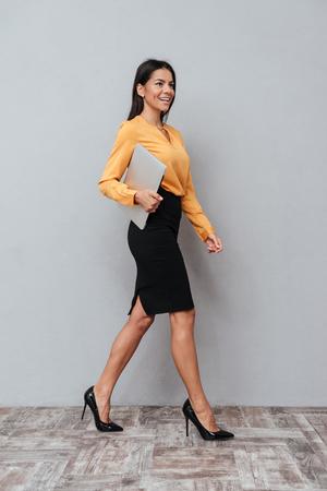 ラップトップを保持していると灰色の背景上に歩いて笑顔満足ビジネスの女性の完全な長さの肖像画 写真素材