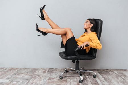 Feliz mujer de negocios alegre sentado en la silla con las manos arriba y divertirse aislado sobre fondo gris