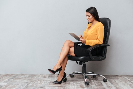 Portrait of a young business woman using tablet for work while sitting in chair isolated over gray background Stock Photo