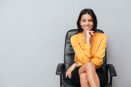 Portrait of a satisfied smiling business woman sitting in chair isolated over gray background