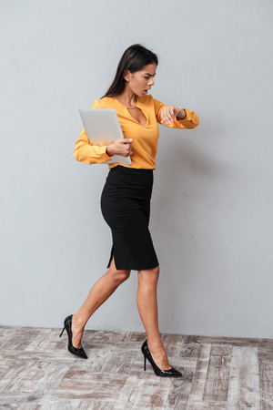 Vertical image of Business woman in suit which walking and holding tablet computer. Full length portrait. Isolated gray background