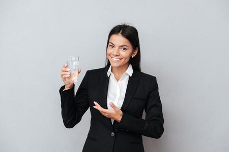 灰色の背景の上彼女の手でミネラルウォーターのガラスを示す笑顔の健全なビジネス女性の肖像画