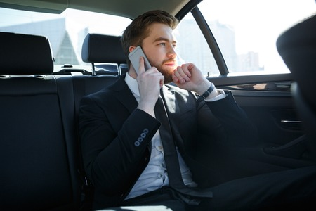 Confident bearded businessman talking on mobile phone and looking away while sitting in the back seat of a car