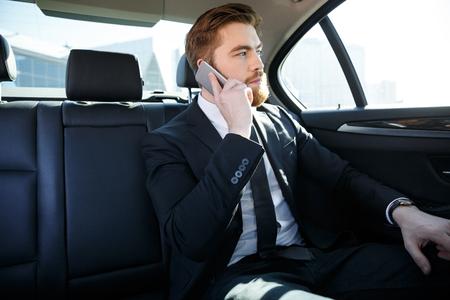 Confiante empresário barbudo falando no celular e desviar o olhar enquanto está sentado no banco de trás de um carro