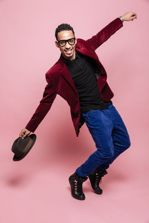 Full length portrait of a stylish afro american man in jacket posing and holding hat isolated on the pink background