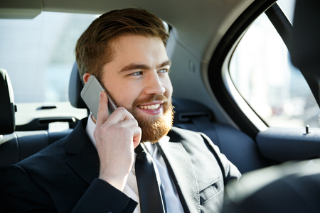Close up portrait of a smiling happy business man talking on mobile phone and looking away in a taxi