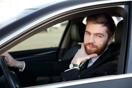 Pensive handsome business man holding hand on chin and driving car