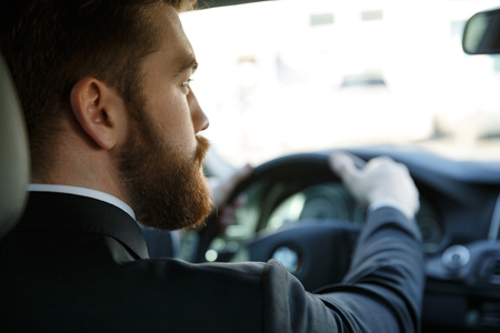 reverse: Back view of a young bearded business man driving car