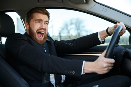 Portrait of a screaming young business man getting into car accident while driving