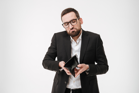 Photo of young sad businessman over white background holding purse without money. Looking aside.