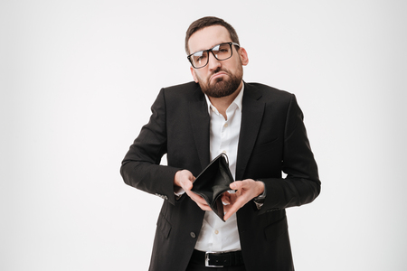 Picture of young sad businessman over white background holding purse without money. Stock Photo