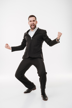 Photo of young happy businessman over white background standing while make winner gesture.