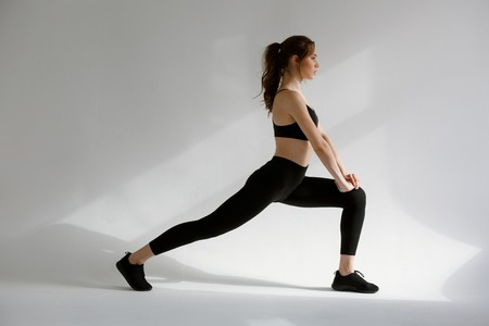 Side view of a young sports woman doing squats isolated on the white background