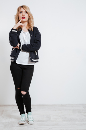 Full length portrait of a pensive cute girl in casual clothes looking away over white background Stock Photo