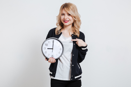 Portrait of a young casual woman pointing finger on wall clock isolated on a white background