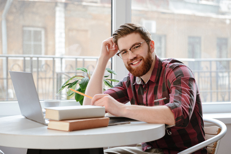 Image of happy bearded young student man sitting in cafe near books while using laptop computer. Looking at camera.