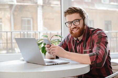 Photo of cheerful bearded young man sitting in cafe chatting by phone while using laptop computer and listening music. Looking at camera. Stock Photo