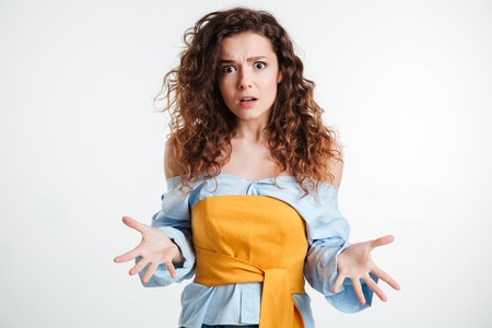 indecisive: Amazed confused young woman gesturing with hands over white background