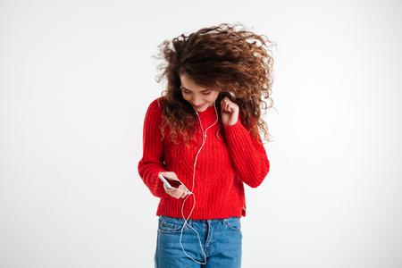 Junge schöne Frau mit Kopfhörern auf weißen Hintergrund tanzen isoliert Standard-Bild - 75935039