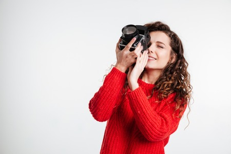 Smiling curly girl with retro camera isolated on the white background Stock Photo