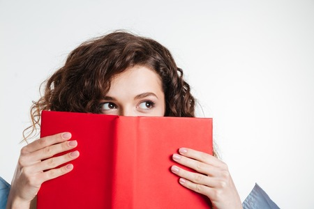 looking away from camera: Close up portrait of a young woman covering her mouth with book and looking away isolated on the white background