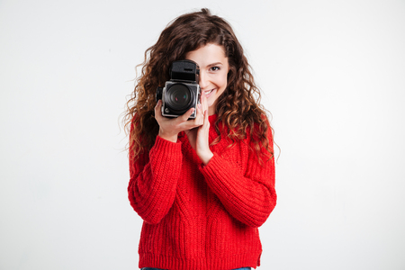 Portrait of a young smiling woman filming with retro camera isolated on the white background Stock Photo