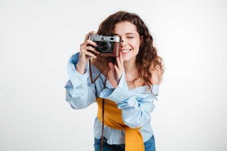 Close up portrait of a young attractive woman with retro camera isolated on the white background