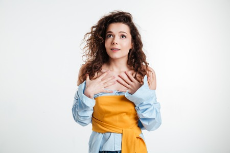 Puzzled young woman holding her hands on her chest while standing isolated on a white background Stock Photo