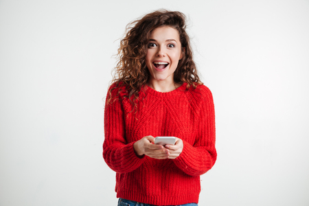 Excited laughing woman in plaid shirt standing and using mobile phone over white background