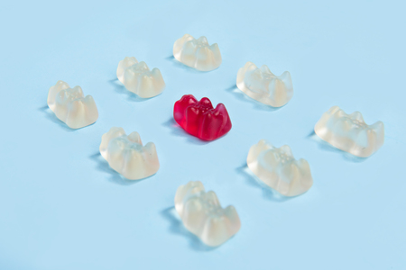 Image of a lot of sweeties chewing candy in teddy bear form over blue table background.