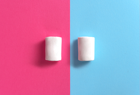 Top view photo of a lot of white sweeties marshmallows over blue and pink table background. Stock Photo