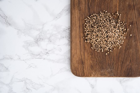 Top view of a spicy white peppercorns heap on a wooden cutting board on white marble background