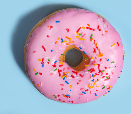 Top view photo of one colorful sweeties donut over blue table background. Stock Photo