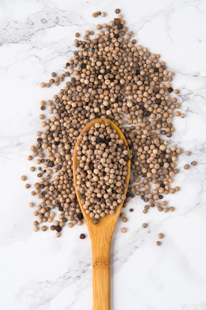 peppercorn: Top view of a wooden spoon full of white peppercorns isolated on white marble background