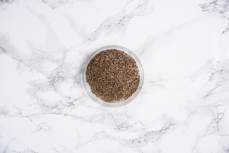 Top view of a natural oat grains in bowl on white marble table