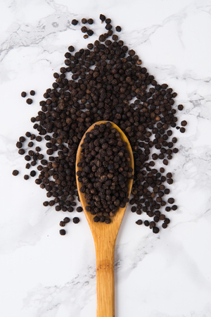 Top view of aa wooden spoon full of black peppercorns isolated on white marble background