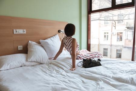 ベッドの上に座って窓を見て美しいの若い女性の背面図