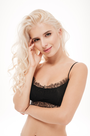 Portrait of a pretty blonde woman standing in black lingerie and looking at camera isolated on a white background