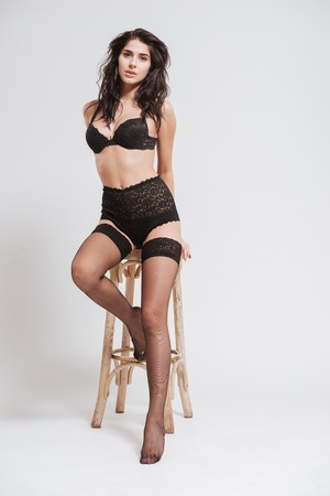 Full length portrait of a sexy charming woman wearing lingerie with stockings and sitting on a chair isolated on a white background
