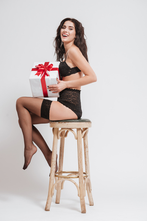 Full length of a young laughing woman in black lingerie with stockings holding gift box and sitting on a chair isolated on a white background