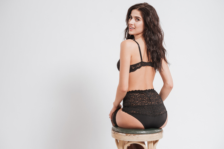 Back view of a smiling beautiful woman in sexy lingerie sitting on a chair and looking at camera isolated on a white background